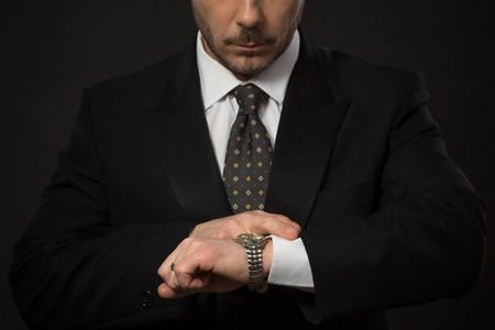 llegar tarde: Closeup portrait of businessman checking time on his hand. Serious man looking at his watch not to be late for work. Studio shot.