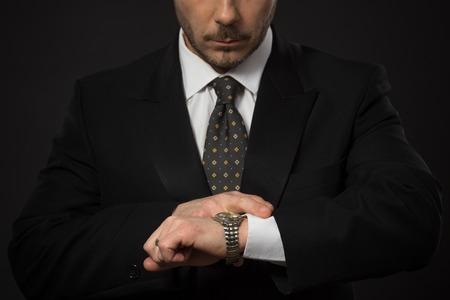 llegar tarde: Retrato de detalle de hombre de negocios que controla el tiempo en su mano. Hombre serio que mira su reloj para no llegar tarde al trabajo. estudio de disparo. Foto de archivo