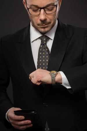 llegar tarde: Retrato de hombre de negocios serio que mira su reloj para no llegar tarde a la reunión de negocios. Hermoso hombre en traje negro con monedero negro con dinero. Foto de archivo