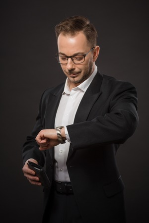 llegar tarde: Portrait of businessman in black suit and glasses checking time. Handsome young man looking at his watch not to be late for business meeting. Foto de archivo