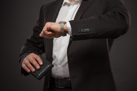llegar tarde: Retrato de detalle de hombre de negocios que mira su reloj y la celebraci�n de pared negro lleno de dinero para no llegar tarde a la reuni�n de negocios.