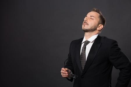 cansancio: Retrato de hombre de negocios posando con los ojos cerrados a causa del cansancio y la fatiga. Tiro del estudio del hombre hermoso sobre fondo gris. Foto de archivo