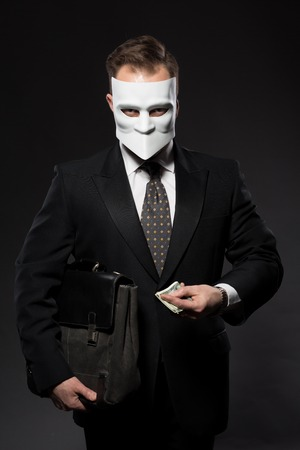 dishonesty: Portrait of businessman in black suit holding money and briefcase. Corruption and fraud concepts. Studio shot.