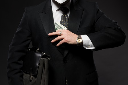 black briefcase: Businessman hiding money in jacket pocket. Corruption and fraud concepts. Man in business suit posing with black briefcase. Stock Photo