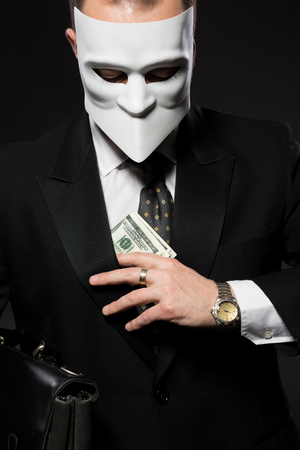 bribing: Businessman hiding money in jacket. Man in mask posing with briefcase demonstrating his independence in studio.