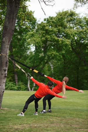 simultaneous: Group of man and woman exercising with suspension trainer in green park on fresh air. Sport couple doing simultaneous exercises.