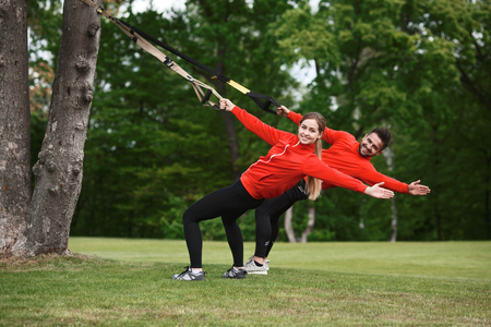 simultaneously: Young attractive woman and man do suspension training with fitness straps outdoors in nature. Group of people training simultaneously.