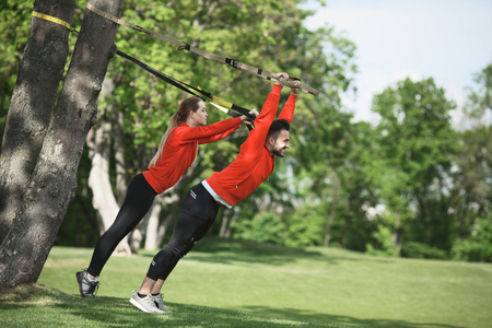 keep fit: Sport man and woman training with suspension trainer sling in park. Man as personal trainer showing his partner how to keep fit. Stock Photo