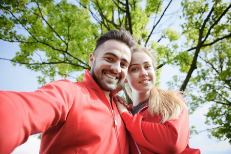 Nice portrait of sport man and woman making selfies in park after or before hard-working training day. Fitness, sports and lifestyle concepts.