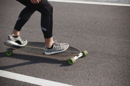 action shot: Man riding on longboard on road. Fitness or sport man resting and relaxing outdoors. Action shot of alongboarder skating on urban road. Stock Photo