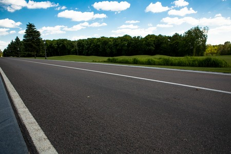 as far as the eye can see: Image of wide open prairie with paved highway stretching out as far as eye can see with beautiful small green hills under bright blue sky in summer time.