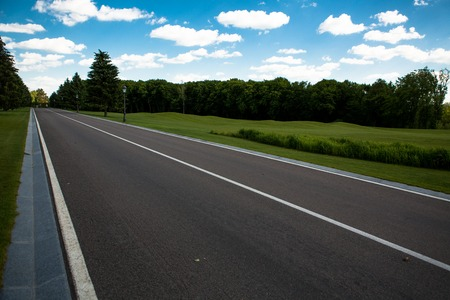 as far as the eye can see: Road panorama on summer evening. Carefree driving on a bright sunny day. Image of wide open prairie with paved highway stretching out as far as eye can see.