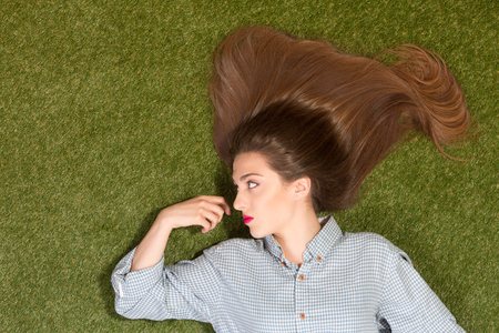 fashion magazine: Beautiful lady with long brown hair lying on green grass and looking at her hand. Pretty woman with red lips posing for fashion magazine. Stock Photo