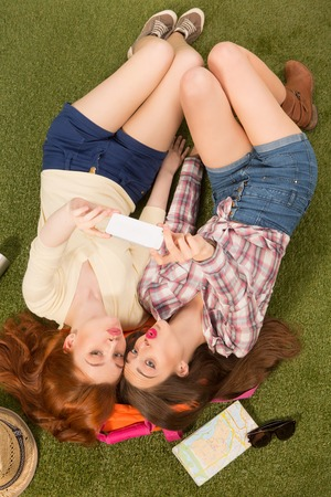selfy: Top view of happy smiling girls making selfies using their mobile or smart phone. Beautiful ladies posing in full length while lying on green grass.