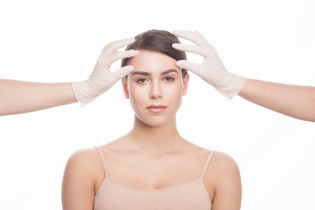 eyes opened: Handmade beauty. Beautiful young woman keeping eyes opened while two hands in medical gloves touching her face isolated on white background. Stock Photo