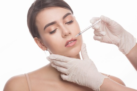 full lips: Closeup of beautiful woman getting injections in her lips. Full lips. Beautiful face and syringe. Plastic surgery and cosmetic injection concepts. Stock Photo