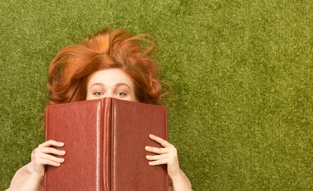 greengrass: Top view of beautiful student girl lying on greengrass with notebook. Pretty woman peparing for her examinations.