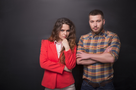freelancers: Portrait of confident business man and woman posing in studio. Freelancers posing with their arms crossed over black background.