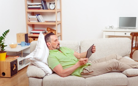 handsom: Portrait of handsome man resting on sofa at home. Happy man lying on sofa or couch and looking at tablet PC. Computer technologies concept.