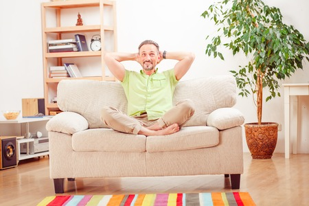 handsom: Portrait of handsome man resting and relaxing on sofa or couch at home. Happy man smiling and laughing for camera.