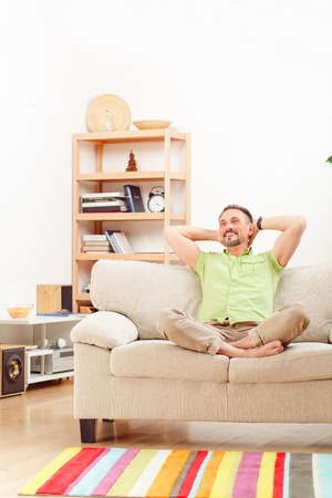 handsom: Happy man smiling and laughing for camera. Portrait of handsome man resting and relaxing on sofa or couch at home. Stock Photo