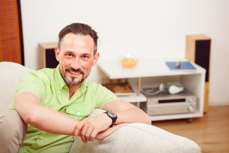 handsom: Closeup portrait of handsome man resting and relaxing on sofa or couch at home. Happy man smiling and laughing for camera. Stock Photo
