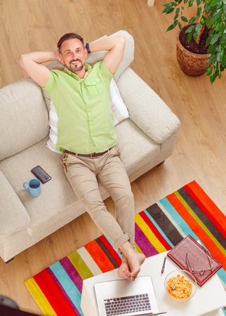 working week: Top view of handsome man lying on sofa or couch resting and relaxing at home after hard working week. Stock Photo