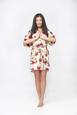 full shot: Picture of fashion asian lady in summer or spring dress in studio clasped her hands in front of her. Happy woman smiling for camera.