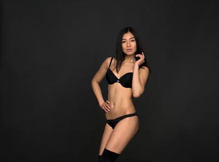 femme noire nue: Portrait de la mode modèle asiatique en lingerie noire en studio. Belle femme regardant la caméra tout en gardant une main sur la hanche.