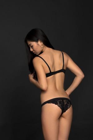 femme noire nue: Photo de mode modèle asiatique en lingerie noire montrant son magnifique retour en studio. Brunette femme regardant vers le bas. Banque d'images