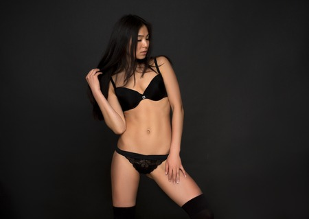 modelos desnudas: Retrato de la mujer hermosa con el pelo negro sobre fondo gris oscuro. Modelo atractivo de la moda asiática en ropa interior o ropa interior negro posando en el estudio.
