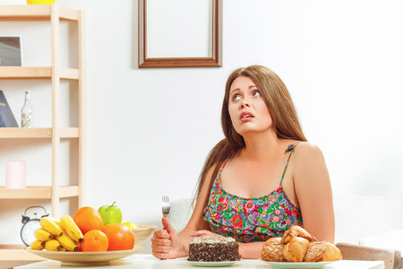 Portrait of fat woman on diet sitting at table with spoon in her hand and thinking whether to eat sweety cake or not at home. Archivio Fotografico