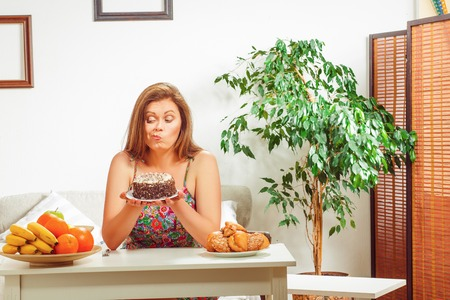 fat food: Diet concept. Beautiful fat woman on diet sitting at table full of healthy and unhealthy dishes at home. Stock Photo