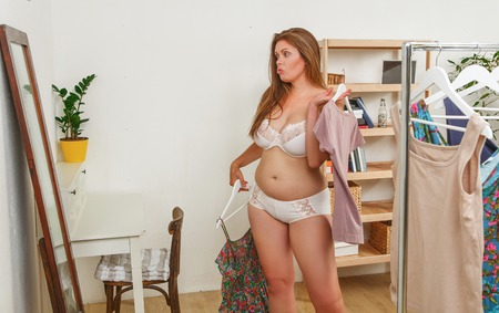 Portrait of fat woman in underwear or lingerie trying dresses at home. Beautiful sad lady looking at camera. Shopping concept.