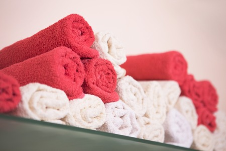 hairdressing saloon: Big bunch of red and white towels in bathroom shelf or hairdressing saloon or beauty saloon.