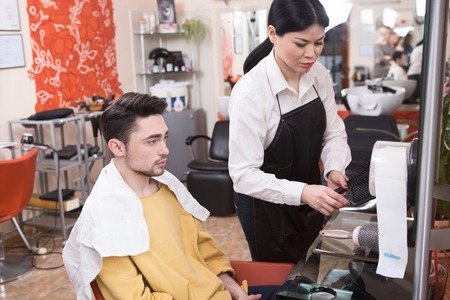 hairdressing saloon: Side view of handsome man sitting in hairdressing saloon. Man having his hair cut by professional hairstylist in modern beauty saloon. Stock Photo