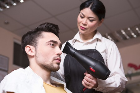 hairdressing saloon: Closeup picture of handsome man hanving his hair dry by professional barber girl in hairdressing saloon. Hair style concept.