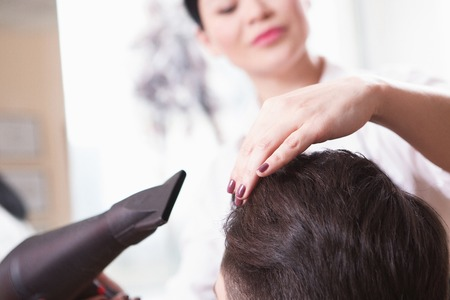 hairdressing saloon: Closeup picture of hairdresser using hair dryer. Young barber girl drying handsome mans hair in hairdressing saloon. Stock Photo