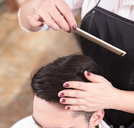 hairdressing saloon: Top view of young man having his hair cut by barber girl. Hairdresser combing handsome mans in hairdressing saloon. Stock Photo