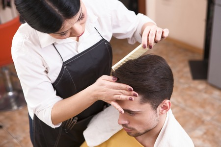 hairdressing saloon: Handsome man having his hair cut by barber girl. View of hairdresser combing handsome mans in hairdressing saloon. Stock Photo