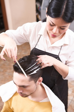 hairdressing saloon: Products of professional cosmetics. Closeup picture of hairdresser making handsome mans man with style in hairdressing saloon. Stock Photo