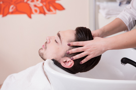 hairdressing saloon: Handsome man having his hair washed in hairdressing saloon. Young man lying with his eyes closed in beauty saloon.