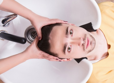 hairdressing saloon: Topview picture of handsome man having his hair washed in hairdressing saloon. Young man lying with his eyes opened andlooking at camera in beauty saloon.