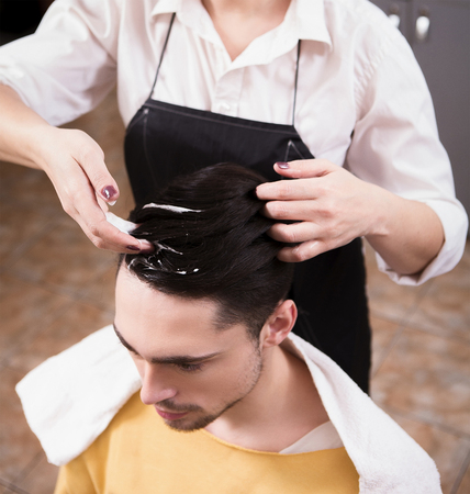 hairdressing saloon: Closeup picture of hairdresser making handsome mans man with style in hairdressing saloon. Products of professional cosmetics. Stock Photo