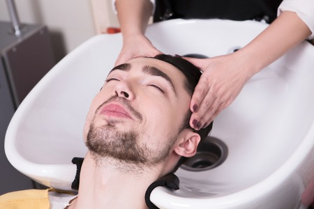 hairdressing saloon: Closeup picture of young man lying with his eyes closed in beauty saloon while having his hair washed in hairdressing saloon.