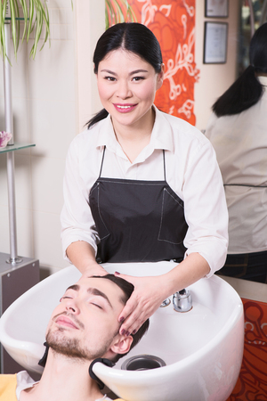 saloon: Hairdresser washing handsome mans hair in beauty saloon. Portrait of handsome man in hairdressing saloon.