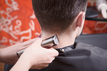 hairdressing saloon: Closeup picture of handsome man having his hair cut with hair clipper in hairdressing saloon. Hairdresser using hair clipper for hair.