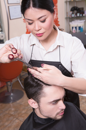hairdressing scissors: Young man in beauty saloon. Cropped shot of female hairdresser cutting mans hair with scissors at hairdressing salon. Stock Photo