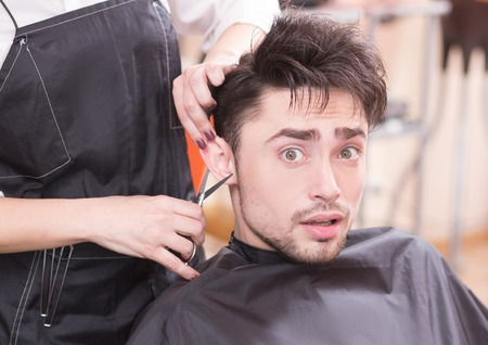 cur: Closeup picture of handsome man having his hair cur by professional hairdresser in hairdressing saloon. Young man looking at camera.
