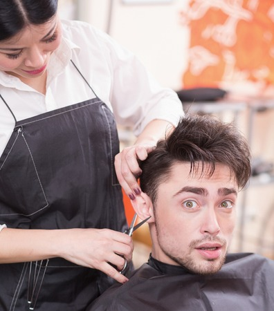 hairdressing saloon: Picture of handsome man having his hair cur by professional hairdresser in hairdressing saloon. Young man looking at camera.